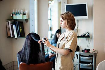 Бразильское выпрямление - мастер обрабатывает локон волос кератином